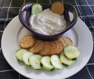 Image purple bowl with cottage cheese dip surrounded by sliced cucumber and round crackers