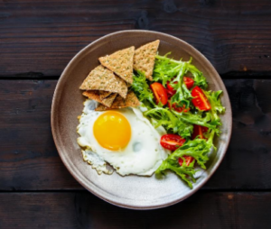 Plate with egg, salad and pita bread on dark table